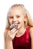 咬住巧克力蛋糕的女孩 免版税库存图片