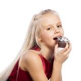 咬住巧克力蛋糕的女孩 免版税库存照片