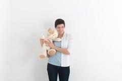 咬住愤怒的长毛绒玩具或玩具熊与缠结和皱眉沮丧的可爱的少妇 库存图片