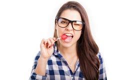 咬住棒棒糖的逗人喜爱的女孩 免版税库存照片