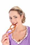 咬住椒盐脆饼的美丽的妇女 免版税图库摄影
