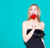 咬住红色棒棒糖和神色的时兴的美丽的女孩在他的 在绿色背景的一件黑礼服在演播室 看Th 免版税库存照片