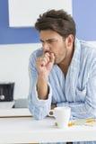 咳嗽与咖啡杯和医学的年轻人在厨台 图库摄影