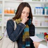咳嗽与药剂师的顾客拿着处方纸和 免版税图库摄影
