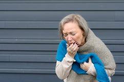 咳嗽入她的手的典雅的资深妇女 免版税库存图片