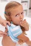 咳嗽医生的小女孩 免版税库存照片