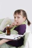 咳嗽和在与医学的床上的女孩 免版税图库摄影