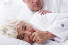 咳嗽在床上的不适的妇女 库存照片