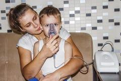 咳嗽的吸入器 妈妈由咳嗽做他的支气管炎的儿子吸入 呼吸在吸入器面具 免版税图库摄影