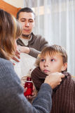 给咳嗽糖浆的夫妇不适的男孩 库存图片