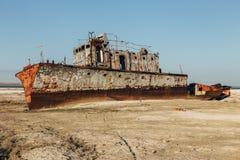 咸海灾害 在沙漠的被放弃的生锈的渔船前咸海地方的  库存图片