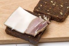 咸烟肉片断在黑麦面包的 免版税库存图片