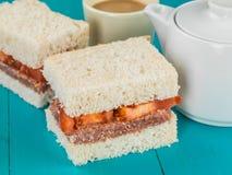 咸牛肉和蕃茄与一个罐的白面包三明治热的茶 图库摄影