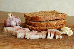 咸猪肉切的烟肉在一块砧板的用大蒜和面包 免版税库存图片