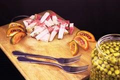咸猪肉油脂用蕃茄和两把叉子在委员会 库存照片