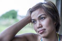 哀伤和体贴的年轻美丽的亚裔妇女剧烈的画象她的看起来去户外的20s或30s的沉思和哀伤 库存照片
