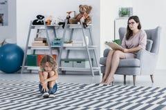 哀伤和孤独的孩子和心理治疗家在治疗期间 库存图片