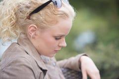 哀伤和孤独的看起来的年轻白肤金发的妇女 库存图片
