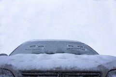 哀伤和幸福微笑在汽车的多雪的挡风玻璃 免版税库存照片