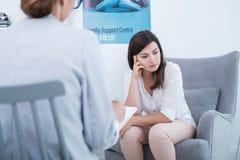 哀伤和担心的母亲谈话与关于她的孩子的一位心理学家 免版税图库摄影
