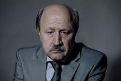 哀伤和沮丧的资深成熟的商业人画象看起来他的60s遭受的消沉的失去的和周道的佩带的neckt 免版税库存照片
