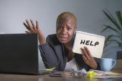 哀伤和沮丧的黑美国黑人的妇女痛苦被注重在办公室与便携式计算机感觉一起使用淹没了要求f 库存照片
