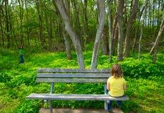 哀伤孤独的孩子看森林坐长凳 免版税图库摄影
