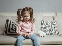 哀伤或恼怒的小女孩,受害者,拿着玩具狗 免版税库存照片