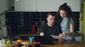 哀伤的不快乐的年轻人在家担心票据付款使用在kithcen的膝上型计算机 他的girlfrend来和支持 股票录像