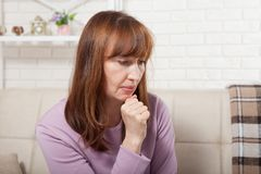 哀伤的中年妇女坐一个沙发在客厅 更年期 库存图片