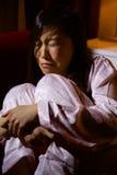 哀伤的亚裔妇女坐哭泣在家庭暴力以后的沙发 免版税库存图片