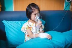 哀伤的亚裔孩子拿着哮喘的治疗的一台面具蒸气吸入器 呼吸通过蒸汽雾化器 图库摄影