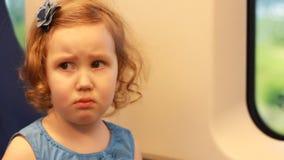 哀伤的儿童女孩乘火车旅行并且表现出牢骚和怨气的情感 股票录像
