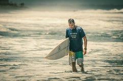 哀伤的冲浪者在水中走 免版税库存照片