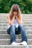 哀伤的十几岁的女孩单独坐台阶 免版税库存照片