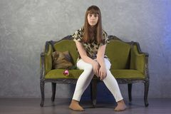 哀伤的十几岁的女孩坐绿色沙发 在灰色背景 工作室 免版税库存图片