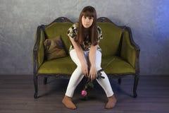 哀伤的十几岁的女孩坐绿色沙发 在灰色背景 工作室 免版税库存照片