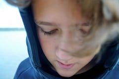 哀伤的十几岁的男孩画象河或湖的银行的 有卷发的逗人喜爱的男孩在佩带在黑hoody的敞篷 库存照片