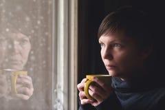 哀伤的单独妇女饮用的咖啡在暗室 免版税图库摄影