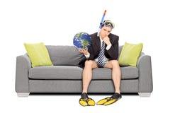 哀伤的商人拿着地球和坐沙发 免版税库存图片
