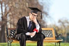 哀伤的大学生坐一条长凳在公园 图库摄影
