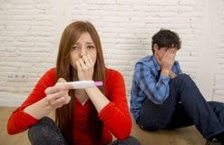 年轻哀伤的夫妇在读桃红色正面妊娠试验的震动和惊奇惊吓了淹没在恐慌 免版税库存照片