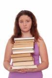 哀伤的女孩举行堆书 免版税库存图片