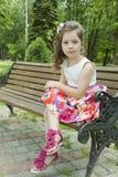 哀伤的女孩在公园坐长凳 免版税库存图片