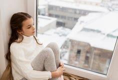 哀伤的女孩在家坐基石窗口在冬天 图库摄影