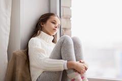 哀伤的女孩在家坐基石窗口在冬天 免版税库存照片