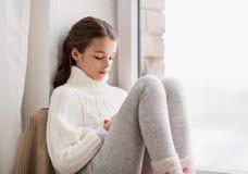 哀伤的女孩在家坐基石窗口在冬天 免版税库存图片