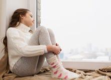 哀伤的女孩在家坐基石窗口在冬天 库存图片