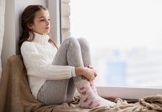 哀伤的女孩在家坐基石窗口在冬天 免版税图库摄影