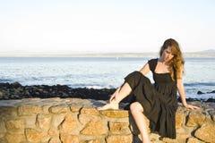 哀伤的女孩坐一个walloverlooking的蒙特里海湾 免版税库存照片